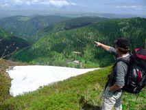duitsland Een wandelaar met een grote rugzak bevindt zich bij een hoogte en kijkt uit in de afstand stock fotografie