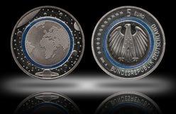 Duitsland vijf euro muntstuk met planeten en blauwe polymeerring stock foto