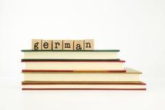 Duitstalig woord op houten zegels en boeken Stock Foto