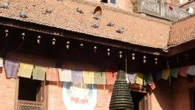 Duiven op dak van de tempelbouw Buitenkant van Boeddhistische tempel met gebed binnen vlaggen op koord en vogels op betegeld dak stock footage