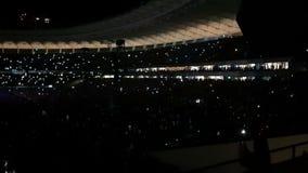 Duizenden mensen die een rots bekijken overleggen en aanstekende flitslichten in slo-mo stock videobeelden