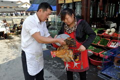 Dujiangyan, China: Cooks Weighing Chicken. Two cooks at a restaurant along the Min River weigh a chicken which will soon be Stock Photography
