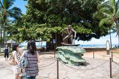 Duke Kahanamoku. Japanese tourists admire Duke Kahanamoku Statue on Waikiki Beach, Honolulu. Duke famously popularized surfing and won gold medals for the USA in Royalty Free Stock Photos