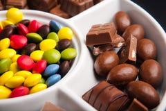 Dulces coloridos del chocolate con los pedazos de chocolate Imagenes de archivo