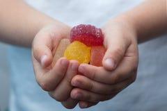 Dulces de la mermelada en manos del niño Imagenes de archivo