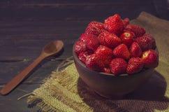 Dulces de verano Las fresas en una arcilla ruedan con una cuchara de madera Fotos de archivo libres de regalías