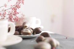 Dulces del chocolate bajo la forma de conchas de berberecho y dos tazas de café fragante Colores claros románticos del desayuno F Imágenes de archivo libres de regalías