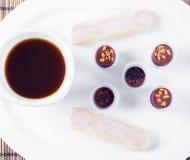 Dulces del chocolate del café de la mañana y galletas del savoyardi en una placa blanca Imagen de archivo libre de regalías