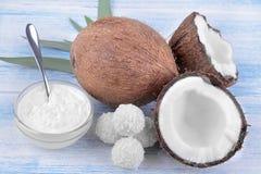 dulces del coco y aceite de coco fresco en un fondo de madera azul Imagenes de archivo