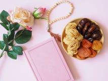 Dulces, fechas, albaricoques secados en una placa en un pinkbackground Flor fotos de archivo