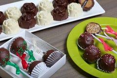 Dulces hechos en casa Dulces recubiertos de chocolate con el relleno de la almendra Estallidos de la torta adornados con un arco  foto de archivo