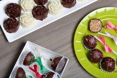 Dulces hechos en casa Dulces recubiertos de chocolate con el relleno de la almendra Estallidos de la torta adornados con un arco  fotos de archivo libres de regalías