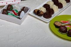 Dulces hechos en casa Dulces recubiertos de chocolate con el relleno de la almendra Estallidos de la torta adornados con un arco  fotos de archivo
