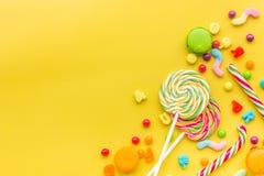 Dulces para el cumpleaños incluyendo la piruleta, macarons y descensos en copyspace amarillo de la opinión superior del fondo Imagen de archivo