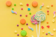 Dulces para el cumpleaños incluyendo la piruleta, macarons y descensos en copyspace amarillo de la opinión superior del fondo Fotografía de archivo libre de regalías