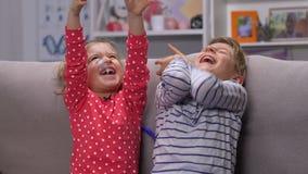 Dulces que caen en los niños felices, niños que cogen los caramelos con el placer, diversión almacen de video