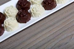 Dulces recubiertos de chocolate con el relleno de la almendra Bajo la forma de flor Mentira en una placa blanca fotografía de archivo