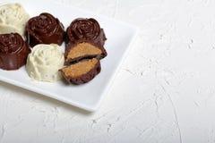 Dulces recubiertos de chocolate con el relleno de la almendra Bajo la forma de flor Mentira en una placa blanca Un caramelo se co imagen de archivo