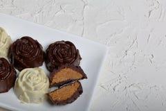 Dulces recubiertos de chocolate con el relleno de la almendra Bajo la forma de flor Mentira en una placa blanca Un caramelo se co fotografía de archivo