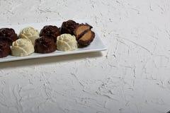 Dulces recubiertos de chocolate con el relleno de la almendra Bajo la forma de flor Mentira en una placa blanca Un caramelo se co foto de archivo