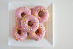 Dulces rosados dulces de cinco buñuelos servidos en un blanco cuadrado Pl fotos de archivo