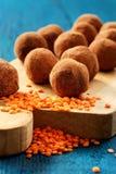 Dulces vegetarianos hechos en casa de la lenteja en polvo de cacao en verraco de madera Foto de archivo