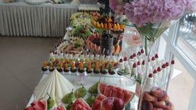 Dulces y frutas adornados deliciosos en las tablas para la recepción nupcial, abastecimiento del partido de cócteles en restauran almacen de video