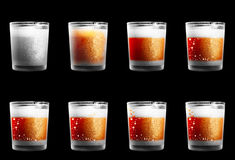 Dull drinking glasses with a texture. Eight small lustreless drinking glasses in different designs isolated to black. Glasses are covered with little water dots Royalty Free Stock Image