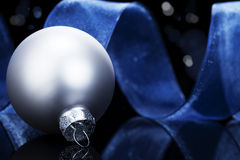 Dull silver christmas ball in front of a blue ribb Stock Photos