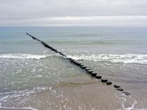 Dull weather and breakwater on the sandy beach Royalty Free Stock Photo