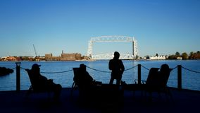 Duluth, MN - October 24, 2018: Friends enjoying a bonfire across the harbor from the Iconic Aerial Lift Bridge. stock video
