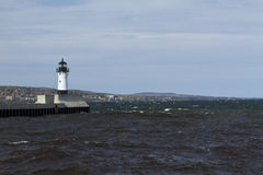 Duluth N Pier Lighthouse. A lighthouse at the end of a breakwater on Lake Superior with Duluth in the background Royalty Free Stock Photos