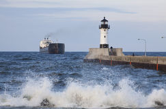 Duluth N Pier Lighthouse & Ship. A freighter ship traveling near lighthouse to enter harbor Stock Photos