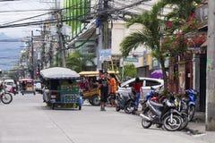 Dumaguete, Filipinas: 13 de maio de 2017: opinião da rua da cidade com transporte local e povos Foto de Stock