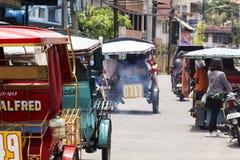 Dumaguete, Filippijnen - 13 Mei 2017: de mening van de stadsstraat met plaatselijke bevolking en driewielers royalty-vrije stock foto's