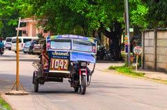 Dumaguete Filippinerna - 13 Maj, 2017: Nationell filippinsk transporttrehjuling på stadsgatan arkivbild
