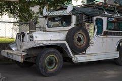 Dumaguete, las Filipinas - 27 de julio de 2018: Jeep blanco del vintage en la calle Escena de la calle en Filipinas fotografía de archivo