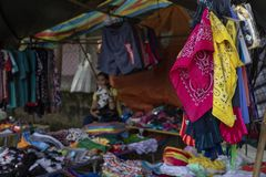 Dumaguete, the Philippines - 27 July 2018: Cheap colorful clothes on local market store. Second hand wear stall. Cheap textile selling. Asian clothes market Stock Photography