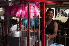 Dumaguete, Philippines - 27 July 2018: Pink cotton candy seller on market stand. Smiling Philippine man selling sweets stock photo