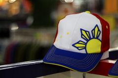 Dumaguete, Philippines - 08 March 2018: Philippine souvenir cap with sun in shop. Gift from Philippines. Summer cap with Philippine flag and sun symbol Royalty Free Stock Images