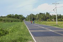 Dumaguete, Philippines - 1 Nov 2017: two bikers on empty road in rice fields. Tropical landscape. Green roadside and blue sky. Rural land scene. Motorbike Stock Image
