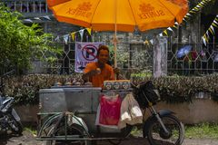 Dumaguete, the Philippines - 10 September 2018: street food seller with mobile stall on motorcycle. Motorbike eatery and man selling food. Streetlife of royalty free stock photo