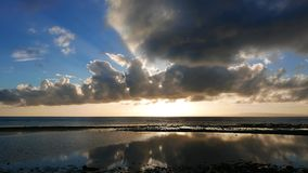 Dumaguete sunrise timelapse. A colorful sunrise video with very low cumulus clouds taken during low tide. Reflection of the moving clouds can be seen in the stock footage