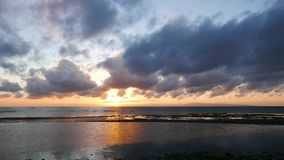 Dumaguete sunrise timelapse. An overcast, colorful sunrise video taken during low tide. Reflection of the moving clouds can be seen in the pools left behind by stock footage