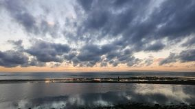 Dumaguete sunrise timelapse. An overcast sunrise video taken during low tide. Reflection of the moving clouds can be seen in the pools left behind by the low stock video footage