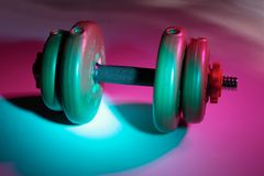 Dumb-bell. Gym weight lit by colour lights Stock Images