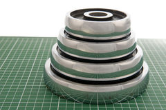 Dumb-bell weights on green floor. Four dumbbell weight plates stacked like pyramid on green floor Royalty Free Stock Image