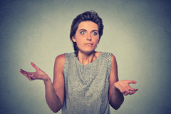 Dumb looking woman arms out shrugs shoulders. Portrait dumb looking woman arms out shrugs shoulders who cares so what I don't know isolated on gray wall Stock Images