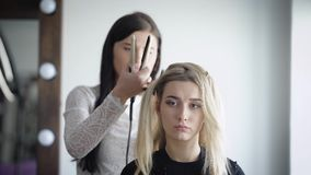 Dumb but very attractive blonde came to a beauty salon to align hair with using a special hairdresser`s equipment stock video footage
