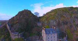 Dumbarton Castle. On the River Clyde in Scotland. Aerial view showing cannons, steps, walls, and building in the cleft of the rock securely blocking access to stock video footage